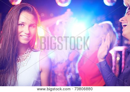 Attractive girl posing on dance-floor in nightclub