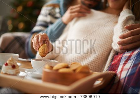 Young restful female with biscuit being embraced by a man during tea time