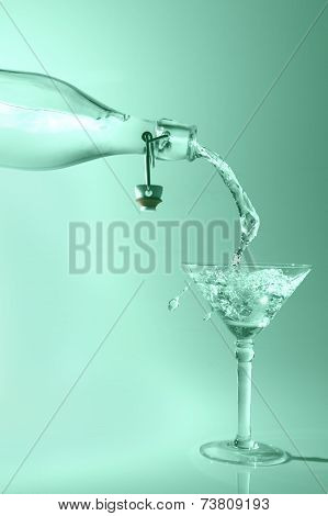 Clear Water Pour Out Of Bottle Splash Into Glass And Spill With Green Back Lighting