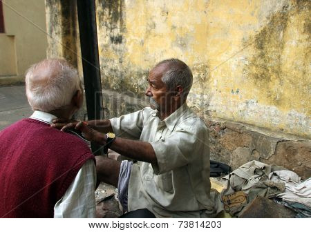 KOLKATA, INDIA - NOVEMBER 30: Street barber shaving a man using an open razor blade on a street in Kolkata, West Bengal, India on Nov 30, 2012
