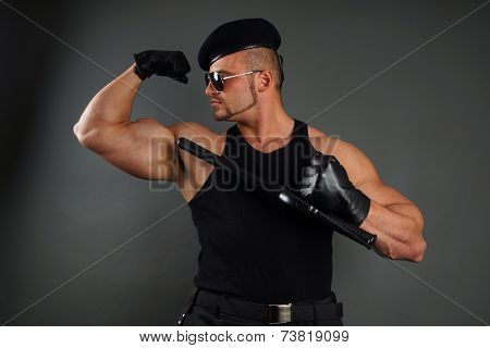 Muscular soldier shows biceps