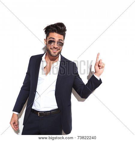 Cool business man wearing sunglasses smiling and pointing up, having a good idea, against a white background