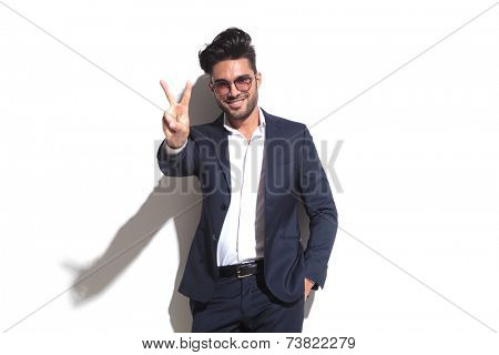 Smiling business man wearing sunglasses showing the victory sign while leaning on a white wall with one hand in his pocket,
