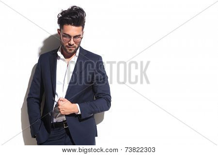 Handsome business man looking down while pulling his jacket and holding one hand in his pocket, leaning on a white wall