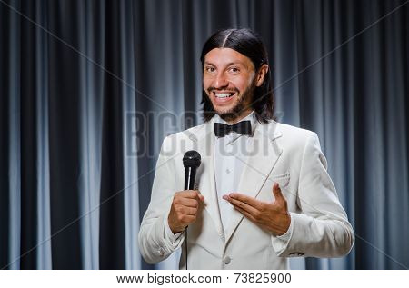 Man singing in front of curtain in karaoke concept