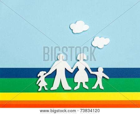 Close up of happy family of paper dolls on colorful background under cutout paper clouds