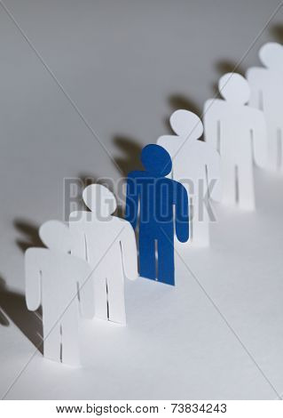 Close up of group of papermen standing in a row. Lots of similar copies of a paper man, but a blue one stands out among them