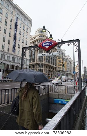 MADRID, SPAIN - OCTOBER 10, 2014: A person walking into the Gran Via Metro Station during the rain in Madrid. The Madrid Metro system is the 8th longest metro in the world and opened in 1919.