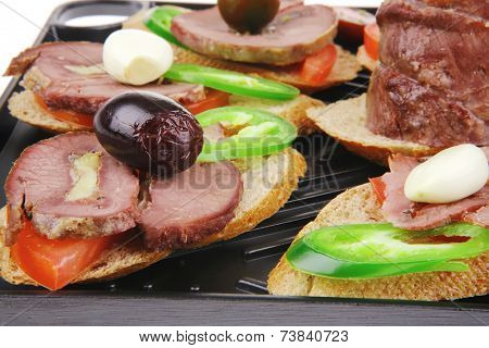 snakes on plate : tartlets with meat and vegetables isolated on white