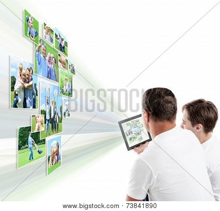 Father And Son Looking Pictures On Tablet
