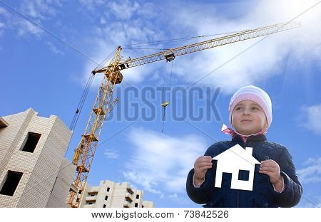 Happy little girl with paper house in hands