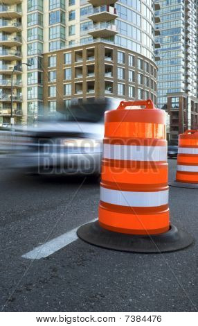 A Vehicle Speeds Past A Large, Orange Traffic Cone.