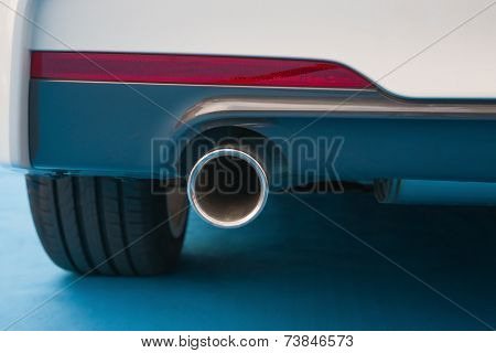 Exhaust Pipe Of A White Car On Blue Carpet