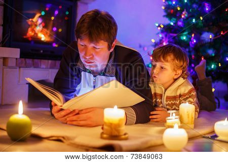 Young Father And His Little Child Reading Book By A Fireplace On Christmas