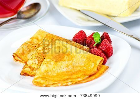 Russian pancakes with black tea and strawberries.