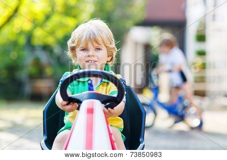 Active Little Child Driving Pedal Car In Summer Garden