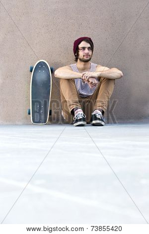 Skateboarder relaxes, lost in thought, sitting on a concrete floor against a granite wall, with his skateboard next to him