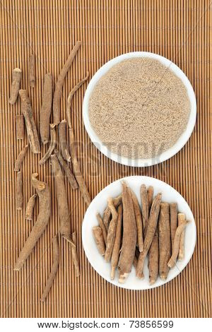 Ginseng ashwagandha herb root and korean powder over bamboo background.