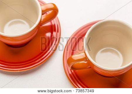 two empty stoneware coffee cups against white tablecloth, shallow depth of filed