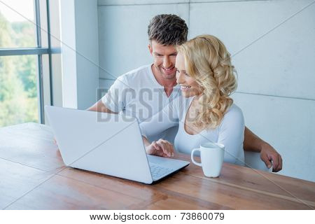 Young couple smiling as they check their social media on the laptop computer while enjoying a morning cup of coffee