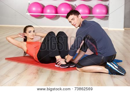Slender fit young woman working out with a handsome male physical trainer at the gym toning her abdominal muscles