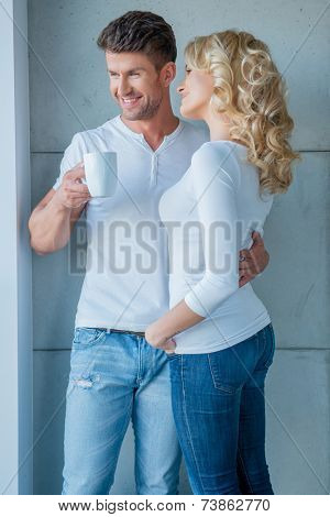 Affection couple standing looking out of a window smiling as they watch something outside while holding their morning coffee