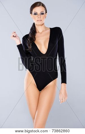 Pretty Long Hair Woman in Black One Piece Long Sleeve Swimsuit Isolated on gray Background.