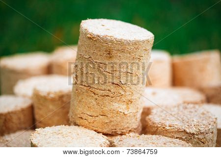 wooden pellets on green grass background