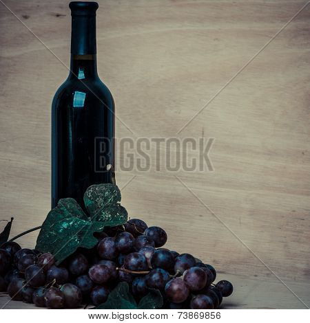 Bottle Of Red Wine And Grapes On Wood Background