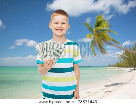 financial, summer, childhood and travel concept - smiling boy holding dollar cash money in his hand over tropical beach background