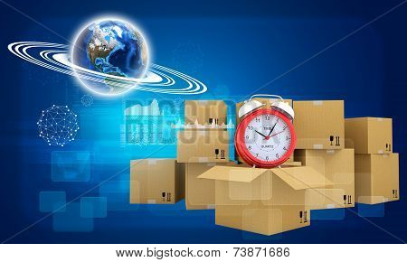 Earth and alarm clock on cardboard boxes