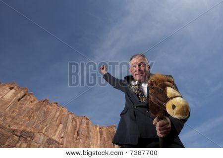 Businessman Riding A Stick Horse