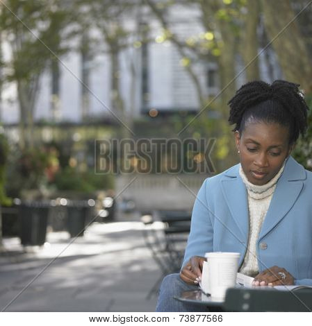 Woman with coffee reading newspaper