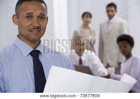 Indian businessman with co-workers in background