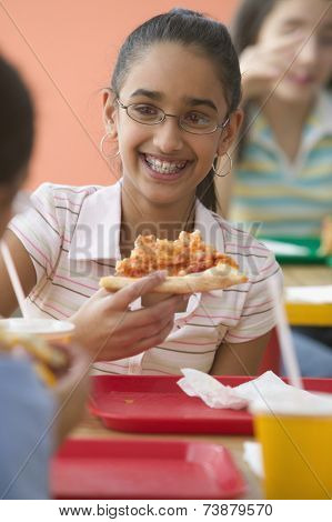 Three girls eating pizza in cafeteria