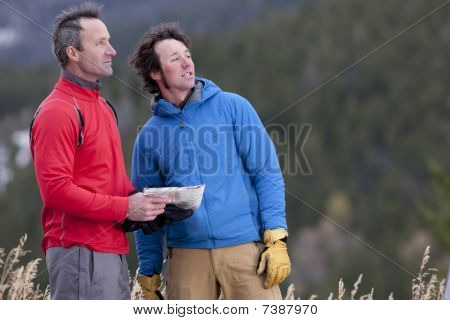 Two Men Standing In The Wilderness With A Map