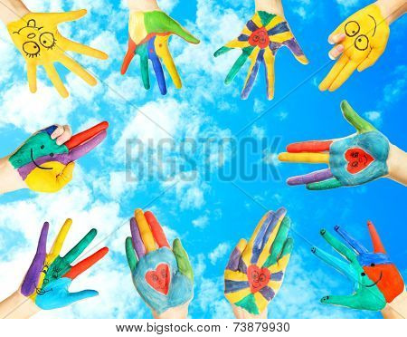 Painted hands on sky background