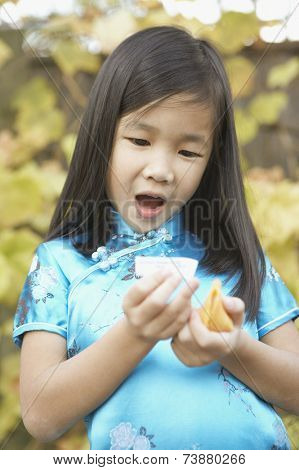 Young Asian girl holding a fortune cookie and reading her fortune