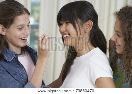 Teenaged girls applying lipstick