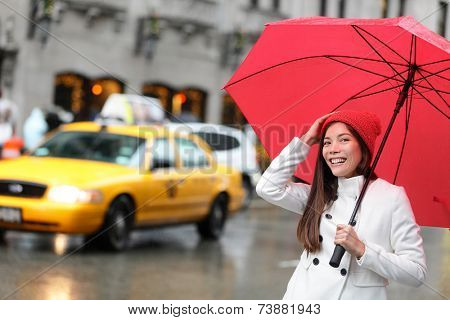 New York City Manhattan woman with fall umbrella walking happy in streets downtown smiling with red umbrella in the rain with yellow taxi cabs. Multiracial urban girl in USA.