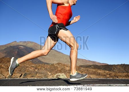 Running man - male runner training outdoors sprinting on mountain road in amazing landscape nature. Close up of fit handsome jogger working out for marathon outside in summer.