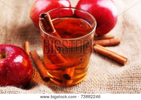 Apple cider with cinnamon sticks and fresh apples on sackcloth background