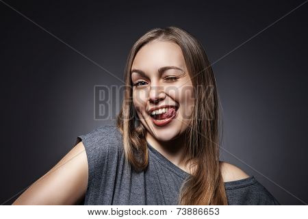 Happy Woman Sticking Out Her Tongue Over Grey