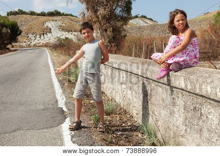 young boy hitchhiking along the street and young girl sits next him