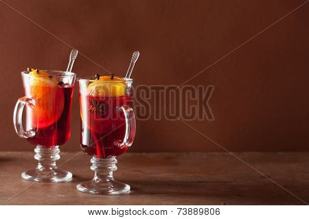 glass of mulled wine with orange and spices, winter background