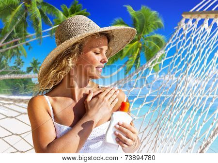 Woman applaying sun protection on skin.