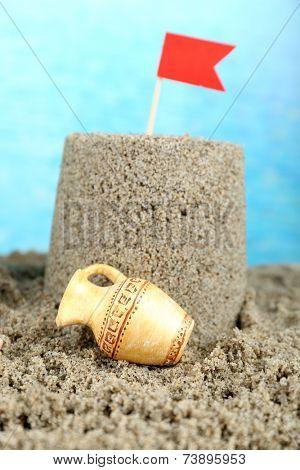 Sandcastle with flag on sandy beach