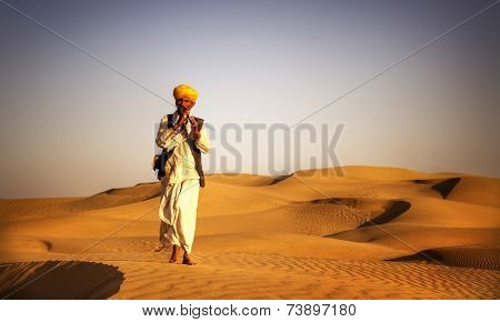 Indigenous Indian man playing wind pipe in a desert.