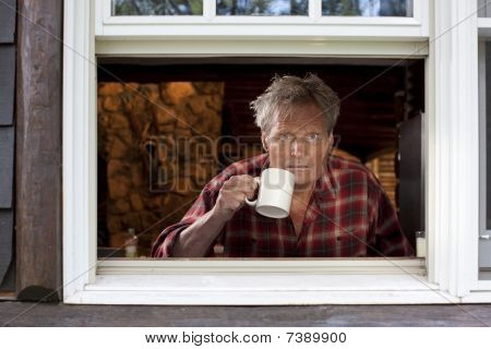 Man With Coffee Cup Looking Out Of Window