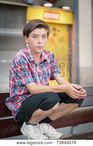Teenage Boy Crouching On A Bench